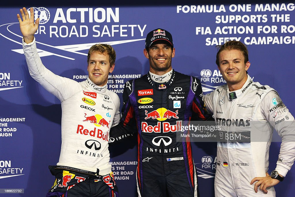 Polesitter Mark Webber (C) of Australia and Infiniti Red Bull Racing celebrates with second placed team mate Sebastian Vettel (L) of Germany and Infiniti Red Bull Racing and third placed Nico Rosberg (R) of Germany and Mercedes GP following qualifying for the Abu Dhabi Formula One Grand Prix at the Yas Marina Circuit on November 2, 2013 in Abu Dhabi, United Arab Emirates.