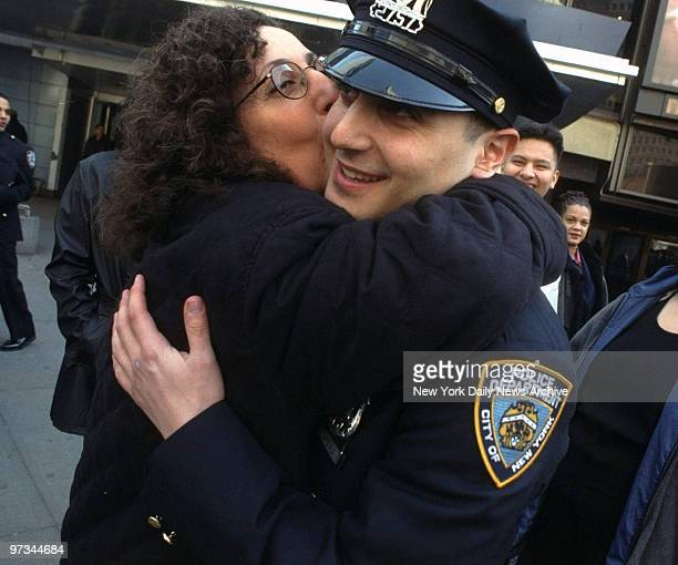 Police Academy graduate Jason Andreula gets a hug and a kiss from his mother Ada as his family looks on outside Madison Square Garden Andreula who...