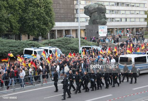 Police accompany a march past the KarlMarx statue organised by the rightwing populist Pro Chemnitz movement on September 14 2018 in Chemnitz the...