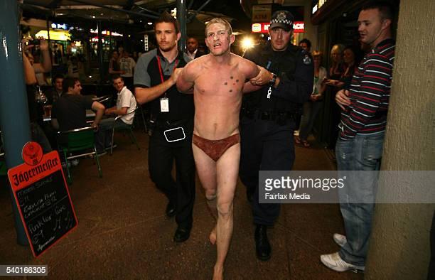 Police accompany a reveller down Cavill Avenue after Friday's fight on the beach FAIRFAX NEWS SURFERS PARADISESCHOOLIES Police escort Nicholas...