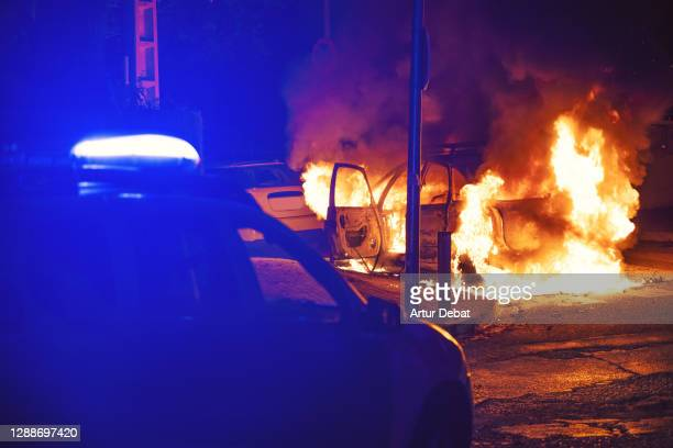 police action during emergency with car in flames at night. - riot stock pictures, royalty-free photos & images