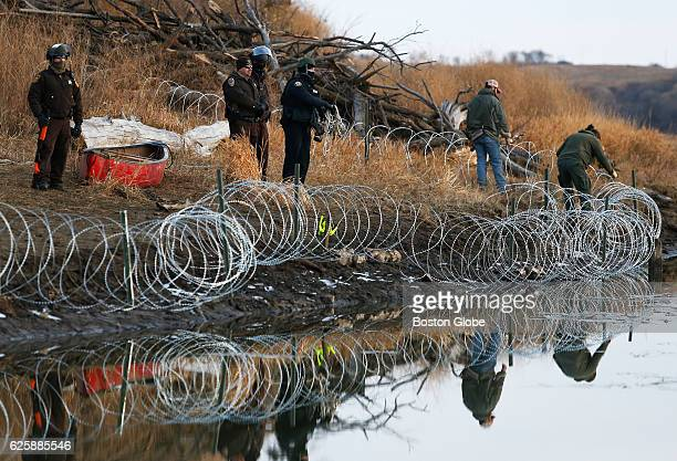 Police adjust barbed wire that they set up on Turtle Island a day after protesters built a bridge to access it in Cannon Ball, ND near Standing Rock...