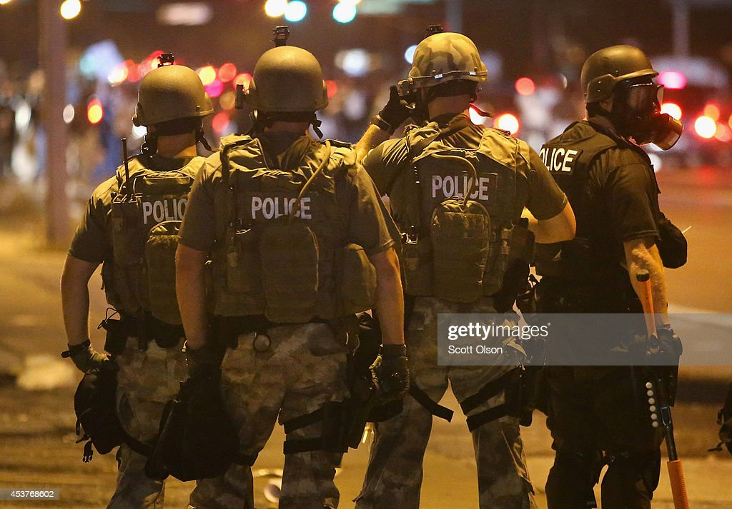 Police advance on demonstrators protesting the killing of teenager Michael Brown on August 17, 2014 in Ferguson, Missouri. Police shot smoke and tear gas into the crowd of several hundred as they advanced near the police command center which has been set up in a shopping mall parking lot. Brown was shot and killed by a Ferguson police officer on August 9. Despite the Brown family's continued call for peaceful demonstrations, violent protests have erupted nearly every night in Ferguson since his death.