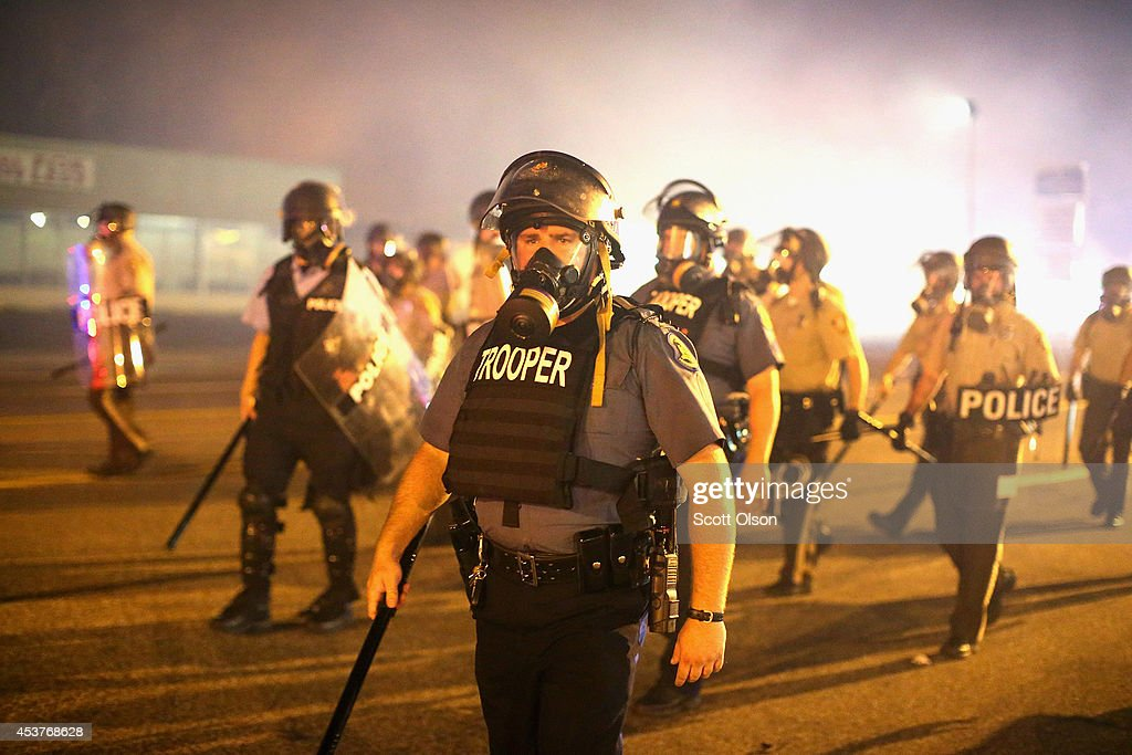 Police advance through a cloud of tear gas toward demonstrators protesting the killing of teenager Michael Brown on August 17, 2014 in Ferguson, Missouri. Police shot smoke and tear gas into the crowd of several hundred as they advanced near the police command center which has been set up in a shopping mall parking lot. Brown was shot and killed by a Ferguson police officer on August 9. Despite the Brown family's continued call for peaceful demonstrations, violent protests have erupted nearly every night in Ferguson since his death.