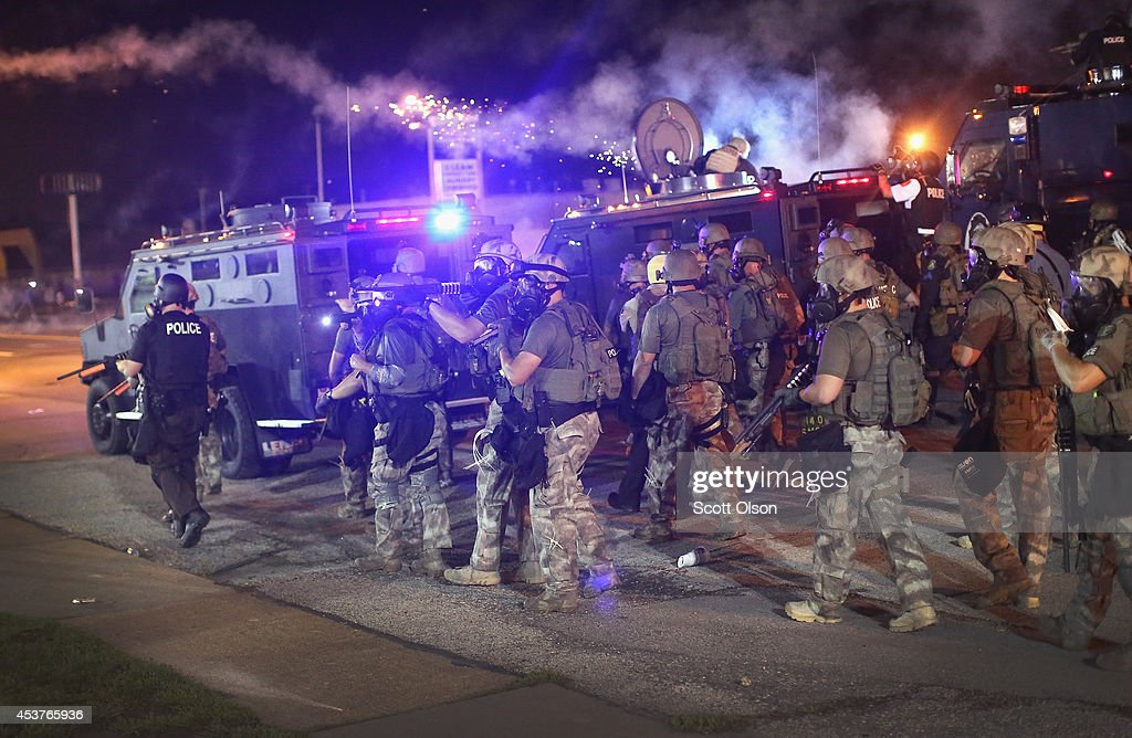 Police advance while sending a volley of tear gas toward demonstrators protesting the killing of teenager Michael Brown on August 17, 2014 in Ferguson, Missouri. Police shot smoke and tear gas into the crowd of several hundred as they advanced near the police command center which has been set up in a shopping mall parking lot. Brown was shot and killed by a Ferguson police officer on August 9. Despite the Brown family's continued call for peaceful demonstrations, violent protests have erupted nearly every night in Ferguson since his death.