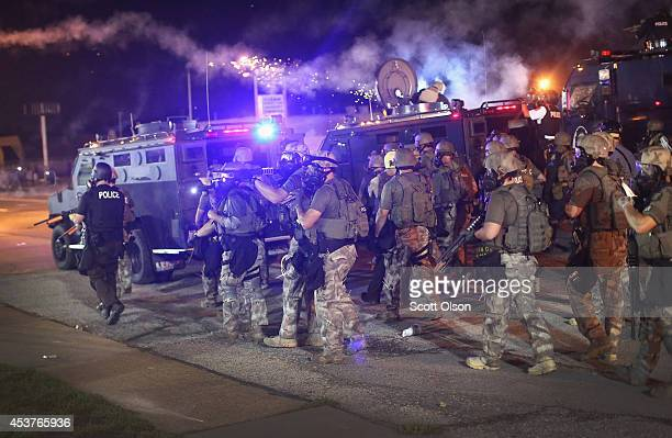 Police advance while sending a volley of tear gas toward demonstrators protesting the killing of teenager Michael Brown on August 17, 2014 in...