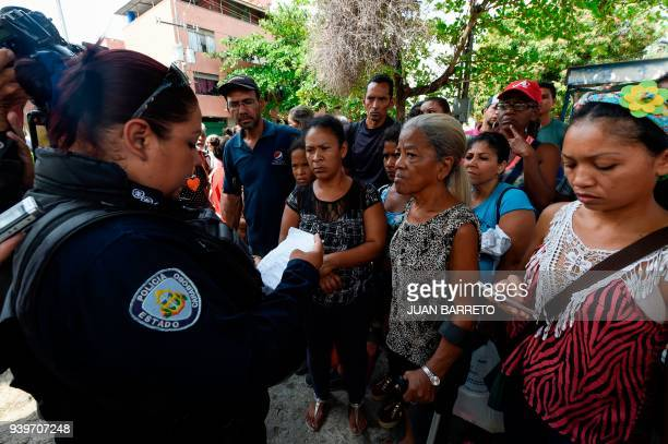 A police agent gives information to the relatives of prisoners waiting outside a police holding cells that caught fire in Valencia northern Carabobo...