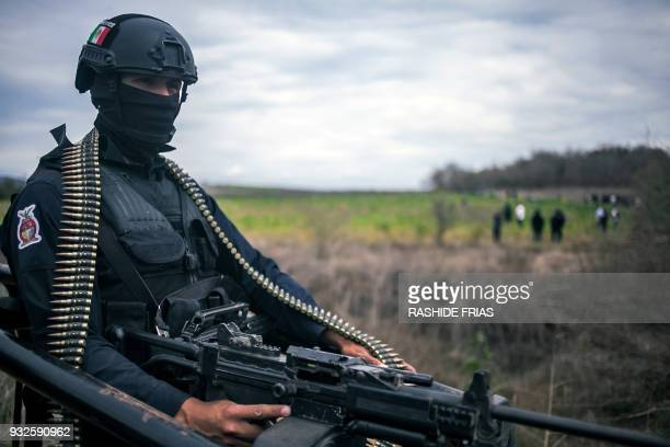 A police agent stands guard during an operation of confiscation of illegal poppy flowers at Los Pericos village Mocorito municipality in Sinaloa...