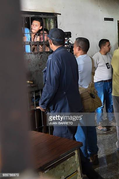Police agents and journalists talk with surviving prisoners at their cell after holding cells caught fire in Valencia northern Carabobo state...