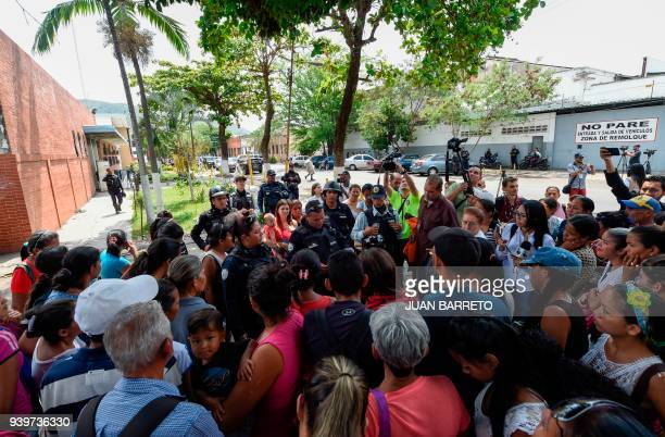 Police agents give information to the relatives of prisoners waiting outside a police holding cells that caught fire in Valencia northern Carabobo...