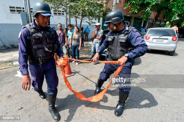 Police agents guard headquarters after a fire engulfed police holding cells while relatives of prisoners wait outside in Valencia northern Carabobo...