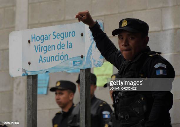 Police agents stand guard next to a sign that reads 'Safe home Virgen de la Asuncion' at the entrance to the children's shelter after 40 girls died...