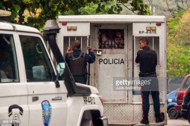 Police agents transport surviving prisoners after police holding cells caught fire in Valencia northern Carabobo state Venezuela on March 29 2018 A...