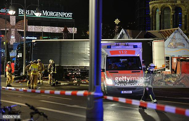Police anbd firefighters work around the truck that crashed into a christmas market at Gedächtniskirche church in Berlin on December 19 2016 killing...