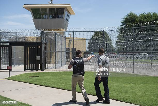 Police and a prison guard patrol the entrance of the El Reno Federal Correctional Institution in El Reno Oklahoma July 16 during a visit by US...