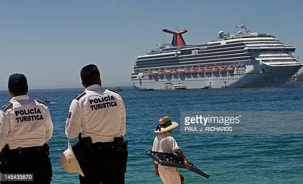 Police and a vendor stand on Medano Beach May 15 2012 as the Carnival Cruise ship Splendor is anchored offshore in Los Cabos Baja California Mexico...
