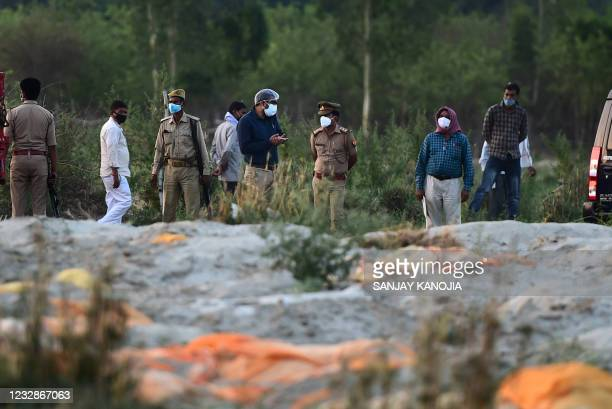 Police and administrative officials inspect a cremation ground on the banks of Ganges River, where suspected bodies of Covid-19 coronavirus victims...
