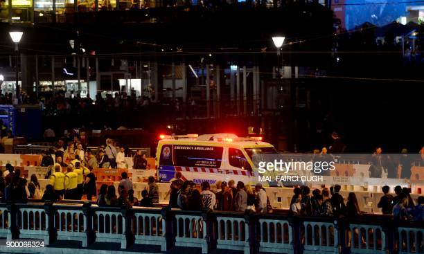 Police and an Ambulance officers are seen on Princes bridge as crowds clear after New Year's eve fireworks in Melbourne December 31 2017 / AFP PHOTO...