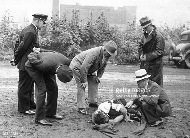 Police and Assistant Attorney William O'Hare inspect the body of murdered gangster James Palermo who was dumped in Astoria Queens