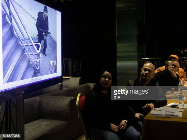 Police and Bureau of Fire officials and Resorts World representatives watch surveillance video footage showing the gunman who on June 2 stormed into...