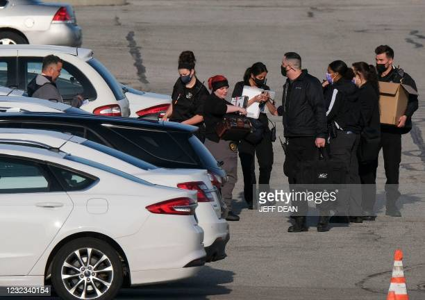 Police and crime scene investigators work at the site of a mass shooting at a FedEx facility in Indianapolis, Indiana on April 16, 2021. - A gunman...
