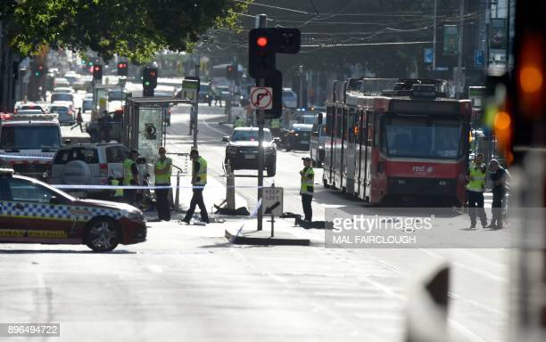 TOPSHOT Police and emergency personnel work at the scene of where a car ran over pedestrians in Flinders Street in Melbourne on December 21 2017 The...