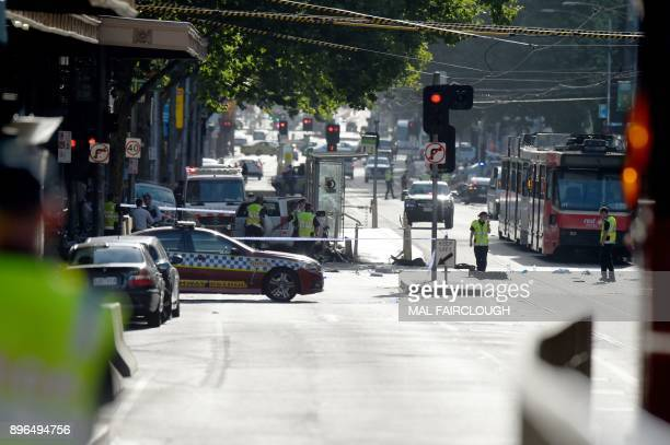 Police and emergency personnel work at the scene of where a car ran over pedestrians in Flinders Street in Melbourne on December 21 2017 The car...