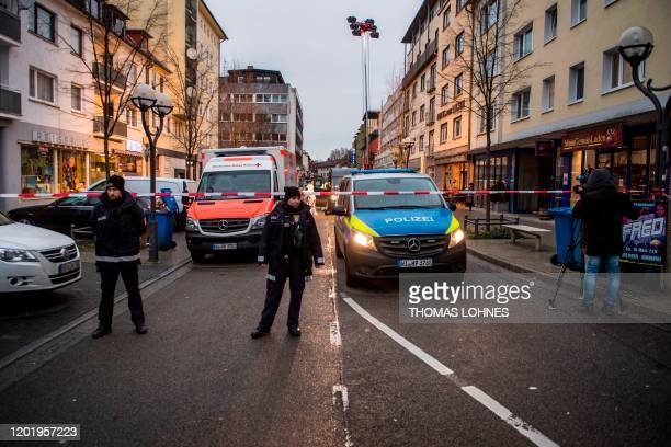 Police and emergency services are seen behind a police cordon near a bar in Hanau near Frankfurt am Main western Germany on February 20 after at...