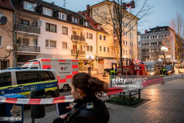 Police and emergency services are seen behind a police cordon near a bar in the centre of Hanau near Frankfurt am Main western Germany on February 20...