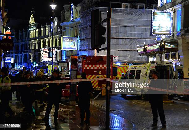 Police and emergency services personnel assist in operations behind a cordon following a ceiling collapse at the Apollo Theatre in Central London on...