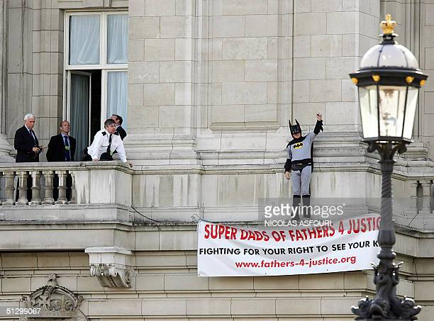 Police and emergency workers negoatiate with Jason Hatch from a balcony on Buckingham Palace in London, 13 September 2004. Hatch a member of the...