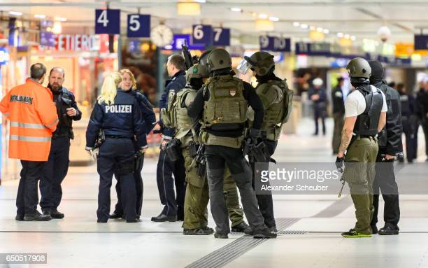 Police and emergency workers stand outside the main railway station following what police described as an axe attack on March 9 2017 in Dusseldorf...