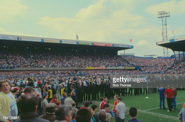 Police and fans on the pitch at Hillsborough football stadium in Sheffield after a human crush at an FA Cup semifinal game between Liverpool and...
