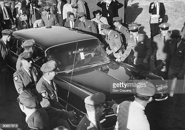 Police and fans surrounding car the Beatles are traveling in from the airport