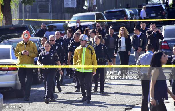 Police and fire authorities walk between roadblocks near Salvadore Castro Middle School in Los Angeles California on February 1 where two students...