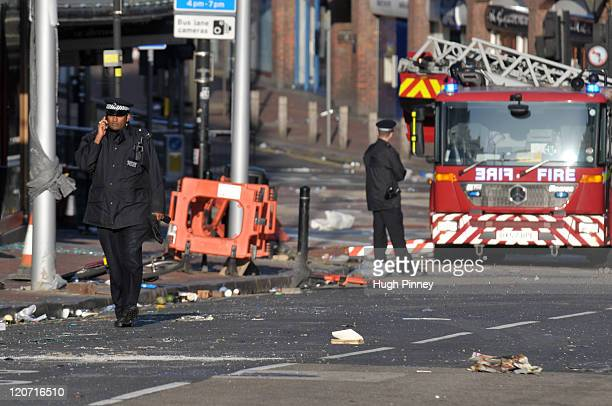 Police and fire crew attend the scene of overnight rioting and looting near Clapham Junction August 9 2011 in London The third night of unrest saw...
