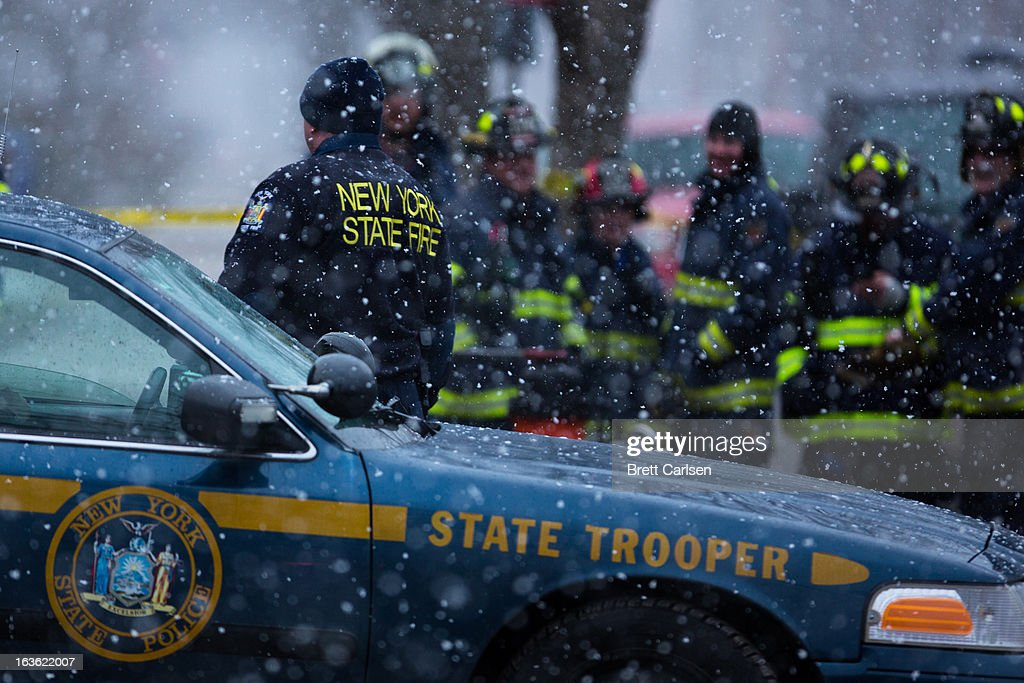 Police and fire crews stand outside the residence of Kurt Meyers, which went up in flames earlier in the day, on March 13, 2013 in Mohawk, New York. Police have identified 64-year-old Kurt Meyers as a possible suspect responsible for a total of four shooting deaths and two injuries across the area earlier in the day.