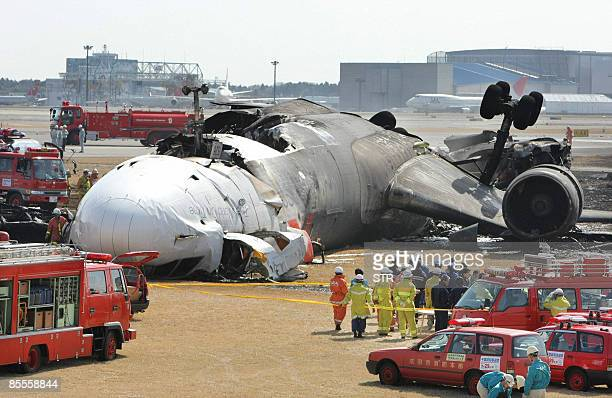 Police and fire fighters inspect a buntout FedEx cargo plane after it crash landed on the runway of the Narita International Airport in Narita city...