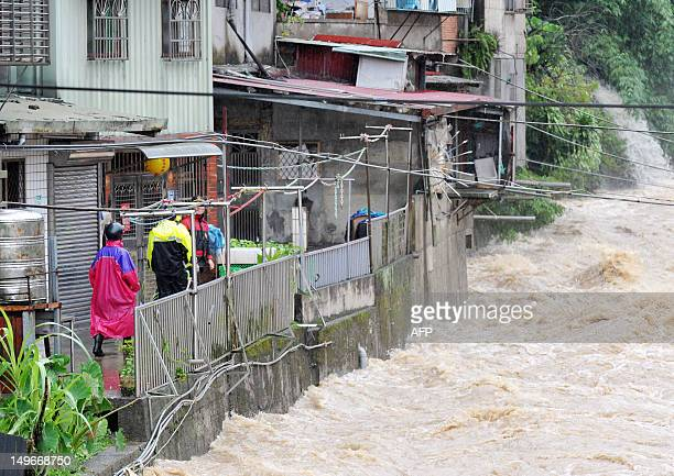 Police and firefighters evacuate local residents near gushing floodwaters in New Taipei City on August 2 2012 Typhoon Saola pounded Taiwan with...