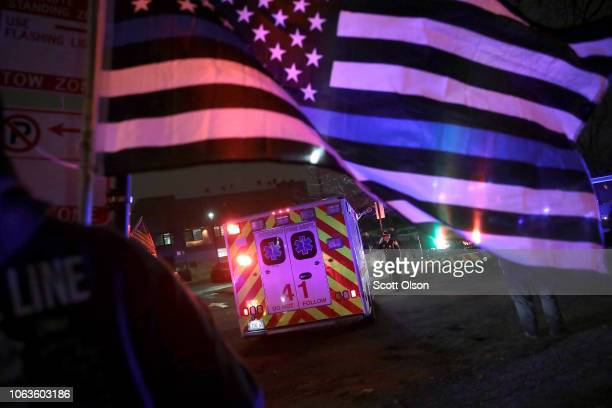 Police and firefighters follow the ambulance carrying the remains of Chicago Police officer Samuel Jimenez as it arrives at the Cook County Medical...