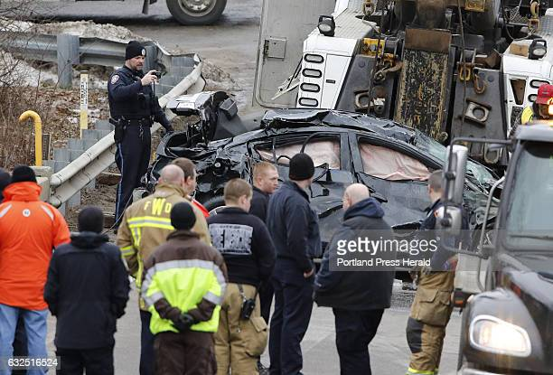 Police and firefighters look over a car that was removed from Stroudwater River along Spring Street Sunday Jan 22 2017 in Westbrook Maine after the...
