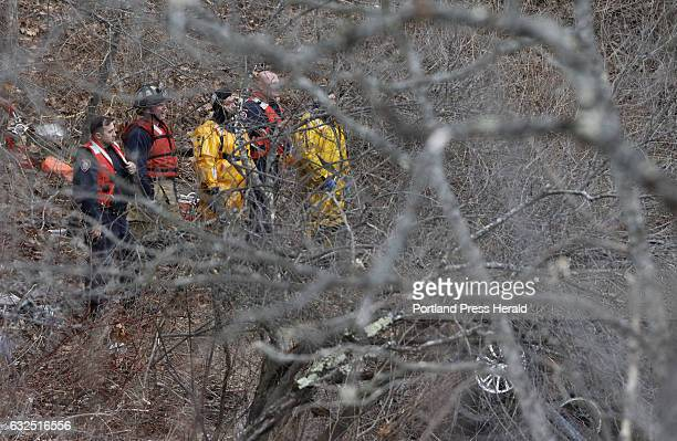 Police and firefighters prepare to remove a car from Stroudwater River along Spring Street Sunday Jan 22 2017 in Westbrook Maine after the car went...