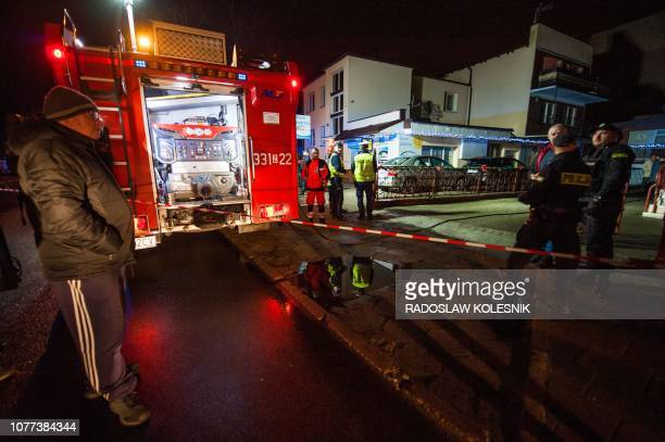 Police and firefighters stand in front of a place where a fire that broke out in an escape room killed five teenage girls in the northern Polish city...
