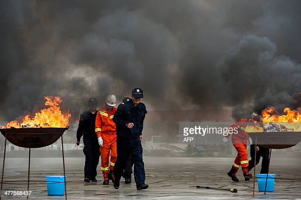 Police and firefighters walk away from smoke as drugs burn in huge iron pots during a ceremony in Ningming county of Chongzuo southwest China's...
