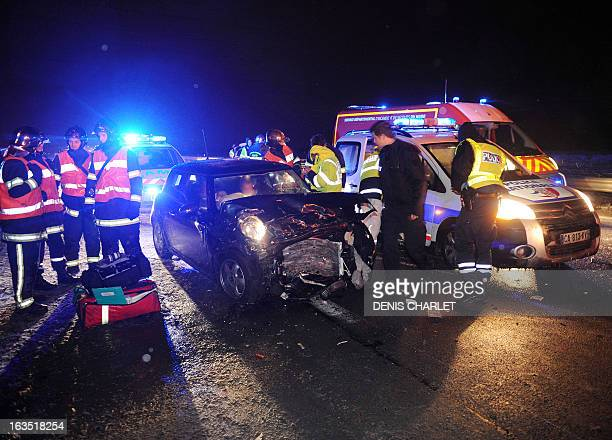 Police and firefighters work at the scene of an accident involving three cars late on March 11 2013 on the A 27 highway near the northern French city...