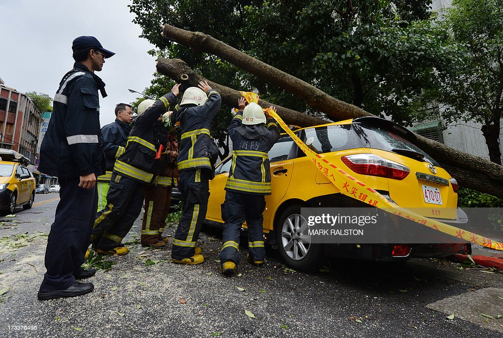 Police and firemen attempt to remove a tree that crushed a taxi after Typhoon Soulik hit Taipei on July 13, 2013. Thousands of people were evacuated in Taiwan and the entire island declared an 'alert zone' as Typhoon Soulik made landfall, killing one person and injuring seven. In the capital Taipei, a 50-year-old police officer died after he was hit in the head by a brick that came loose during the typhoon, the Central Emergency Operation Centre said. AFP PHOTO/Mark RALSTON