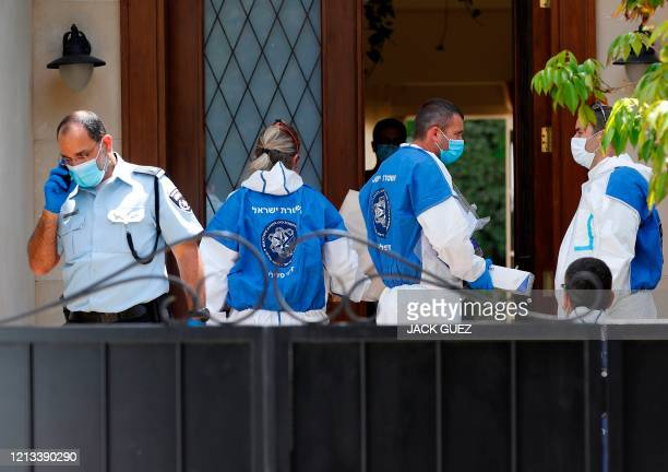 Police and forensic experts gather at the entrance of the residence of Israel's Chinese ambassador on the outskirts of Tel Aviv after he was found...