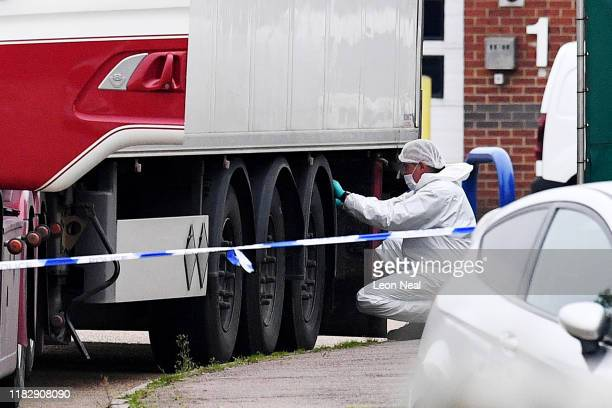 Police and forensic officers investigate a lorry in which 39 bodies were discovered in the trailer, as they prepare move the vehicle from the site on...