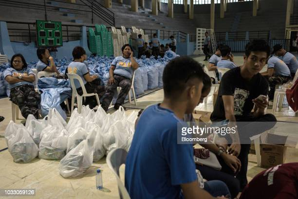 Police and government personnel sit next to bags of relief supplies at a makeshift disaster relief operations center ahead of Typhoon Mangkhut's...