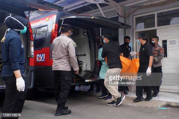 Police and hospital officials load body bags of victims to an ambulance to be transported to a police hospital in Tangerang on September 8 after a...